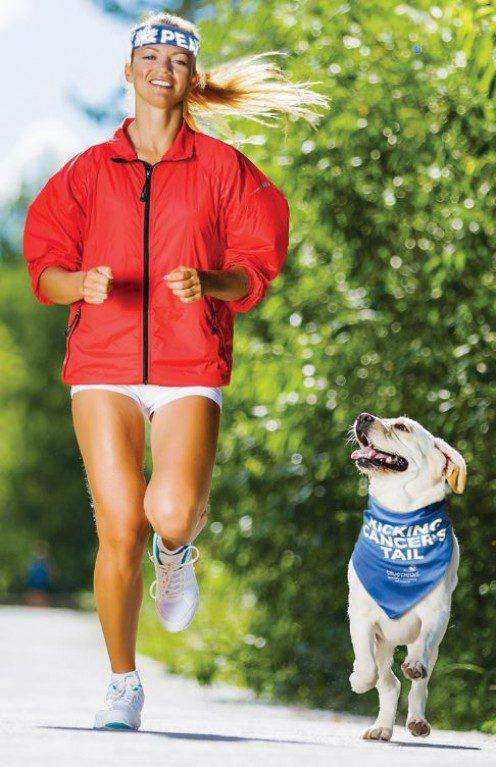 woman and dog running while wearing bandanna